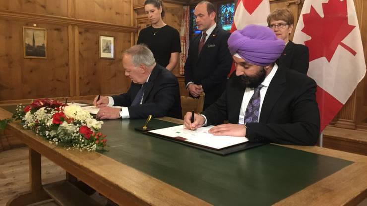 Wirtschaftsminister Schneider-Ammann und sein kanadischer Amtskollege Bains unterzeichnen in Davos eine gemeinsame Absichtserklärung.