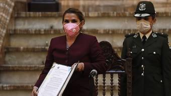 Jeanine Anez, Übergangspräsidentin von Bolivien, posiert mit dem Dokument, das das neue Gesetz enthält. Die bolivianische Übergangspräsidentin hat ein Gesetz verabschiedet, das die Wahl eines neuen Präsidenten und eines neuen Parlaments bis zum 18. Oktober festlegt. Foto: Juan Karita/AP/dpa