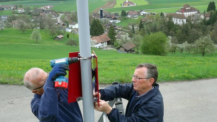 Peter Kunz und Res Schärer montieren «Herzroute Seetal»-Schilder oberhalb von Schloss Hilfikon.