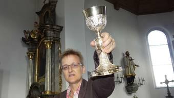 Edith Hunziker von der Kantonalen Denkmalpflege Aargau zeigt hier den kleineren der beiden Schönauer Messkelche aus dem Oeschger Kirchenschatz. – Foto: chr