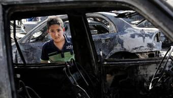 Ein Junge blickt in ein Auto, das bei einem Anschlag zerstört wurde