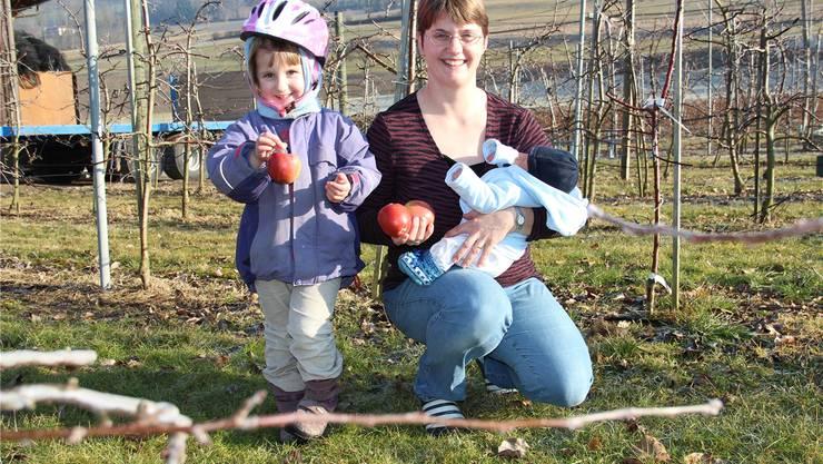 Mirjam Wietlisbach zeigt mit Rahel (4) und Dominik (9 Tage) ihren Obstgarten neben dem Haus. aw