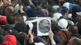 Ein Teilnehmer an der Beerdigung des ermordeten Oppositionspolitikers Belaid hält dessen Foto hoch