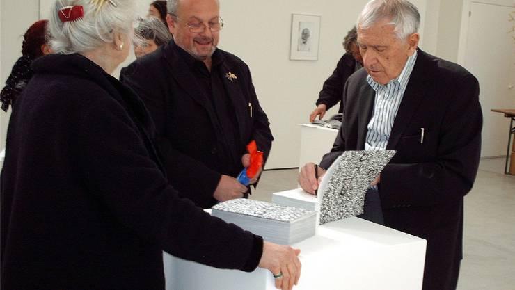 Leonardo Bezzola (rechts) signiert sein drittes Fotoalbum «Clic 3» im Haus der Kunst in Solothurn.