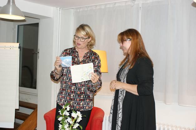 Claudia Hauser (r) übergibt Sybil Schreiber eine Nepal-Broschüre