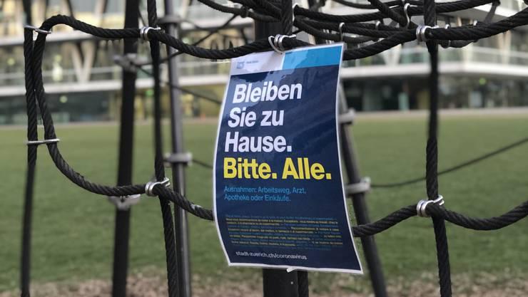 Spielplatz vor dem Schulhaus Leutschenbach mit Appel der Stadt Zürich, bitte zu Hause zu bleiben.