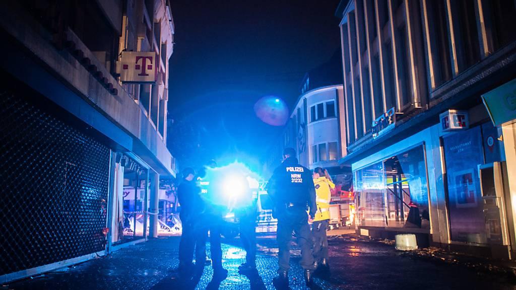 Polizisten gehen durch die zerstörte Innenstadt von Kirchheim in Nordrhein-Westfalen, um Plünderungen zu verhindern. Hier hatten heftige Regenfälle in der Nacht für Schlammlawinen und Überflutungen gesorgt. Kanzlerin Merkel hat den Betroffenen der Hochwasserkatastrophe rasche Hilfe versprochen. Foto: Jonas Güttler/dpa