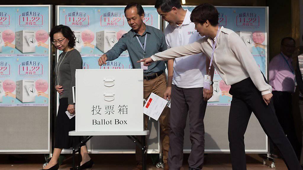 Demokratie will gelernt sein: Mitarbeiter von Hongkongs Regierungschef Leung Chun-ying (weisses Hemd) zeigen ihm, wo man den Stimmzettel in die Urne stecken kann.