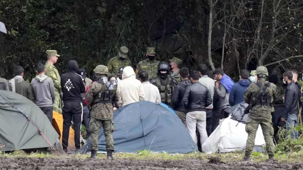 dpatopbilder - ARCHIV - Migranten, die an der Grenze zu Belarus festsitzen, werden von polnischen Beamten umstellt. Polens Grenzschützer haben im September an der Grenze zu Belarus rund 3200 Versuche einer illegalen Einreise registriert. Foto: Czarek Sokolowski/AP/dpa