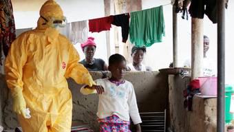 Ein Helfer begleitet ein Mädchen, das Ebola-Symptome aufweist.