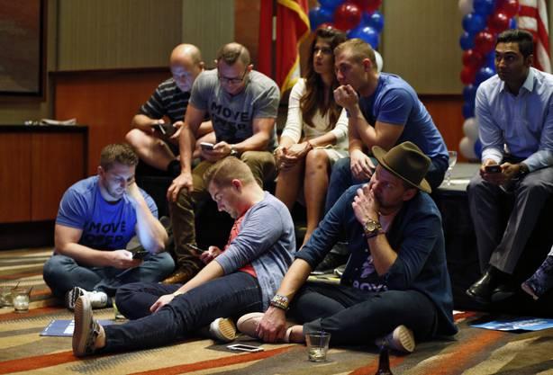 Sie ahnen die Niederlage: Anhänger der Demokraten haben sich an einer Wahlveranstaltung in Dallas auf den Boden gesetzt und starren gebannt auf ihre Smartphones.