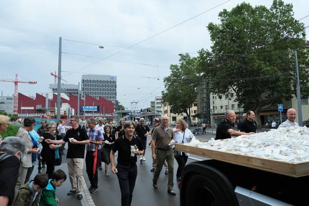Dahinter verteilen Mitglieder des Fest-OKs und Schlieremer Stadträte Taschentücher für Freudentränen und Gummibärchen.