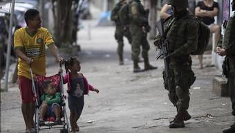 Anwohner gehen an Soldaten vorbei, die den Eingang einer Favela bewachen. Rund 5000 Polizisten und Soldaten sind in mehreren Armenvierteln von Rio de Janeiro gegen bewaffnete Banden vorgegangen.