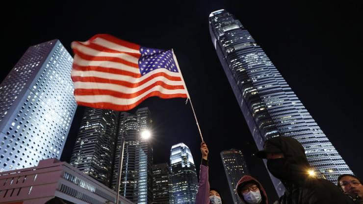 Protestierende in Hongkong schwenken die US-Fahne als Reaktion zum Entscheid des US-Präsidenten.