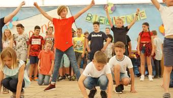 Schülerinnen und Schüler singen und rappen über ihre Freude am neuen Schulhaus.