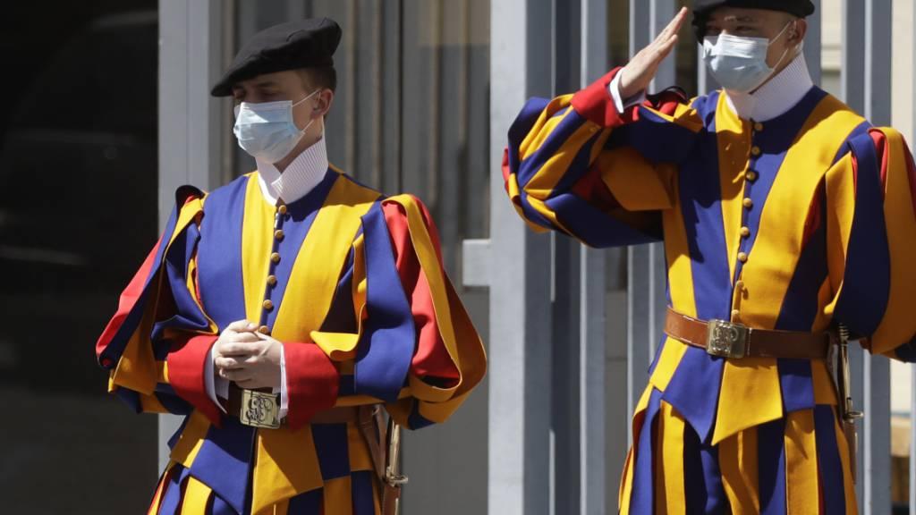 ARCHIV - Zwei uniformierte Gardisten der Päpstlichen Schweizergarde stehen mit Mund-Nasen-Schutz am Eingang zum Vatikan. Foto: Alessandra Tarantino/AP/dpa