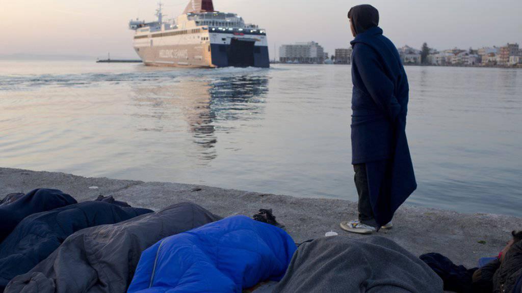 Ein pakistanischer Flüchtling schaut einer Fähre nach, die den Hafen der griechischen Insel Chios in Richtung Türkei verlässt. Nach dem Willen der EU-Kommission sollen die Flüchtlinge künftig besser in Europa verteilt werden. (Archiv)