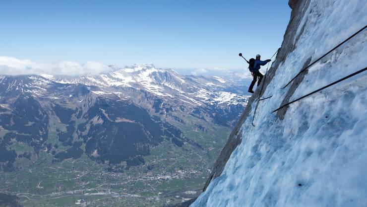 Mammut Pro Alpinist Dani Arnold trägt den Kamerarucksack durch den Hinterstoisser Quergang in der Eiger Nordwand.