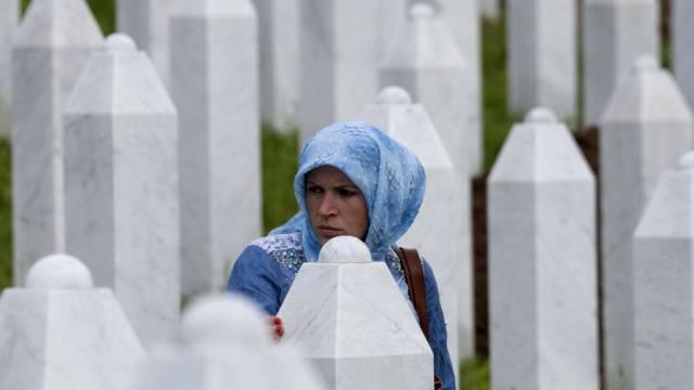 Eine muslimische Frau zwischen Grabsteinen in Srebrenica