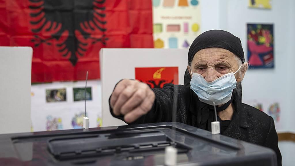 Eine Frau wirft in Tirana ihren Stimmzettel in eine Wahlurne. Foto: Visar Kryeziu/AP/dpa