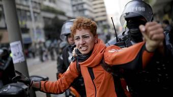 Kolumbianische Polizisten nehmen in der Hauptstadt Bogotá einen Anti-Regierungsdemonstranten fest.