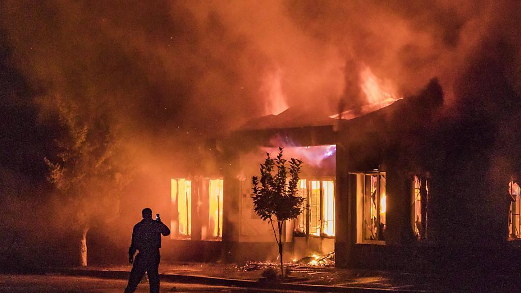 Ein Mann fotografiert mit einem Handy den Brand eines Gebäudes, nach dem Einschlag einer aserbaidschanischen Rakete.