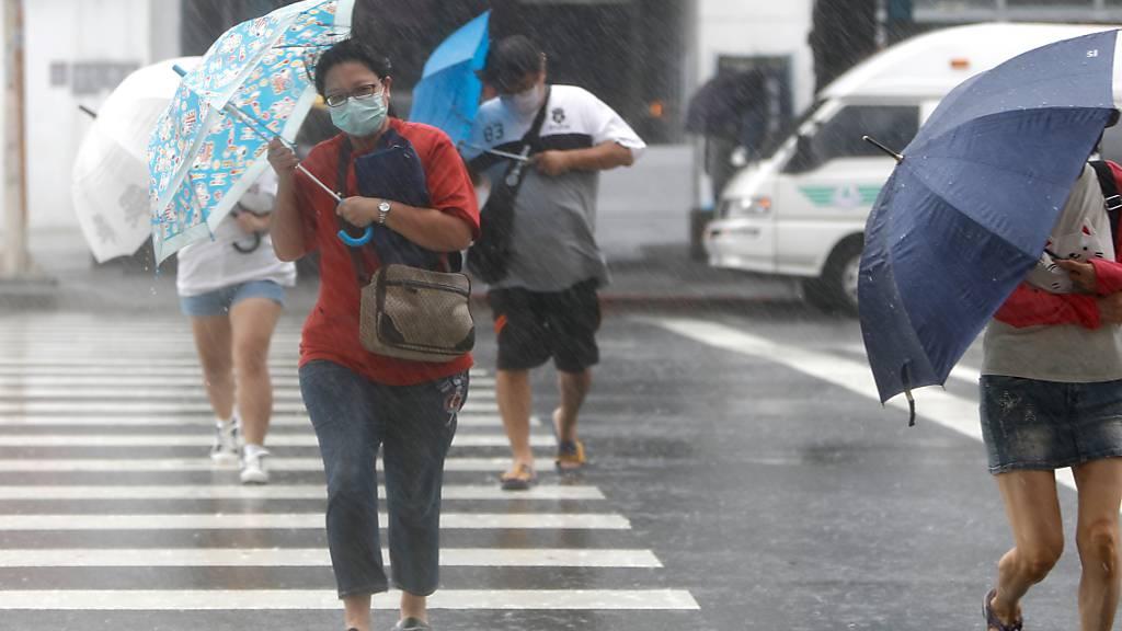 Menschen mit Regenschirmen überqueren bei starkem Wind und Regen einen Zebrastreifen in Keelung. Foto: Daniel Ceng Shou-Yi/ZUMA Press Wire/dpa