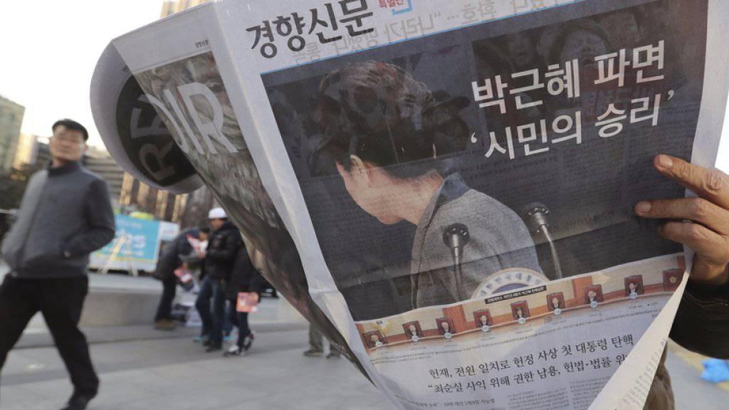 Mann am Freitag in Seoul mit Zeitung, die das Ende von Parks Präsidentschaft in Südkorea verkündet.