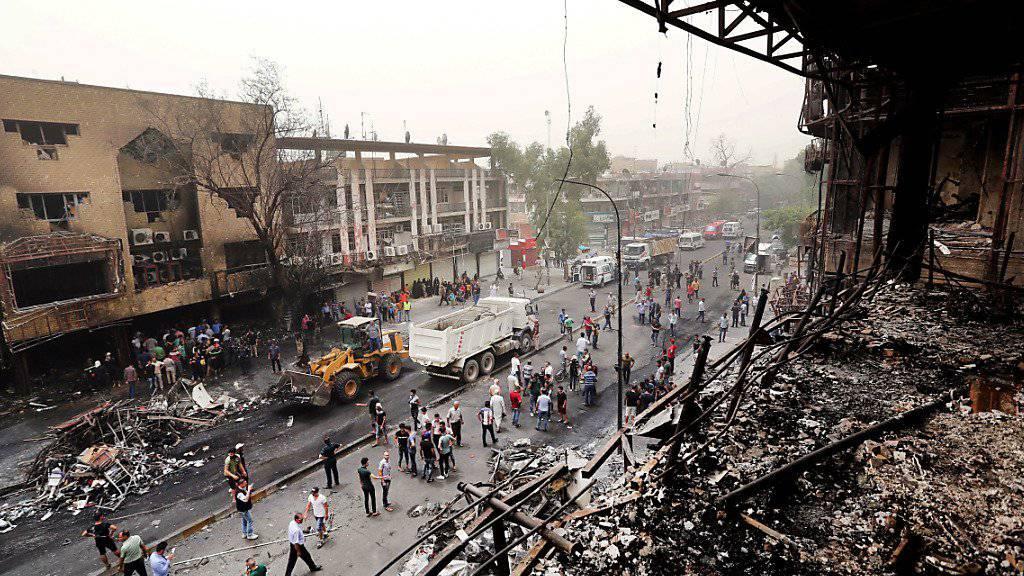 Sicherheitskräfte und Zivilisten schauen sich den Schaden am Tatort im Geschäftsviertel Karrada an.
