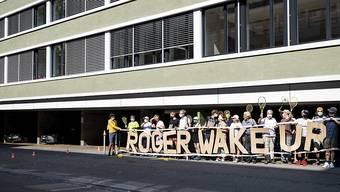 """In Zürich demonstrierten Vertreterinnen und Vertreter der Koalition """"Roger Wake Up Now"""" vor dem Sitz der Roger Federer Foundation."""