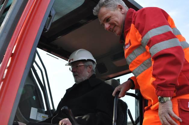 Rolf Senn wird instruiert wie man Bagger fährt