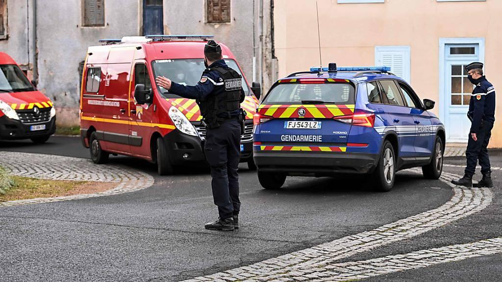 Ein Polizist regelt den Verkehr für vorbeifahrende Einsatzfahrzeuge der Feuerwehr. In einem französischen Dorf hat ein Mann laut Agenturberichten drei Polizisten erschossen. Foto: Olivier Chassignole/AFP/dpa