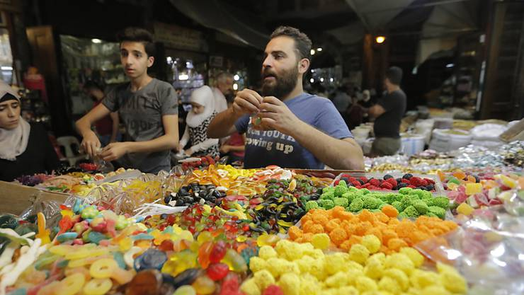 Die Menschen in Syrien decken sich auf einem Markt in Damaskus mit Süssigkeiten ein für Eid al-Fitr, das Fastenbrechen nach dem Ramadan.