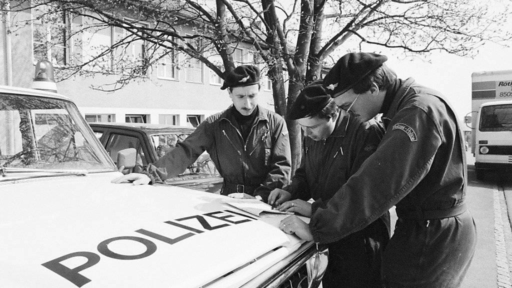 Polizisten besprechen sich zur Suche nach der verschwundenen Edith Trittenbass vor deren Schulhaus in Wolfikon. (Archivbild)