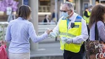 Mitarbeiter der Verkehrsbetriebe Zürich (VBZ) verteilen an der Tramhaltestelle Bellevue Hygienemasken an die Fahrgäste.
