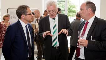 Baden-Württembergs Ministerpräsident Winfried Kretschmann (Mitte) zu Besuch im Aargau. Regierungsrat Urs Hofmann und Grossrat Markus Dieth hören gespannt zu.