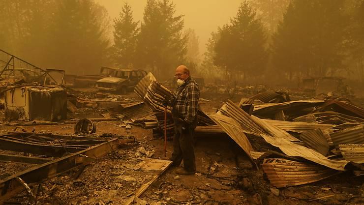 George Coble geht durch die Überreste seines Hauses im Bundesstaat Oregon, das durch einen Waldbrand zerstört wurde. Foto: John Locher/AP/dpa