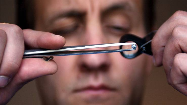 Ein Juwelier untersucht einen Diamanten, eine begehrte Beute. Keystone