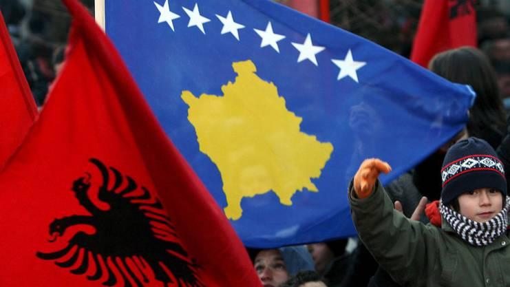 Rot mit Doppeladler: die albanische Flagge. Die Kosovarische zeigt die Umrisse des Landes auf blauem Hintergrund. Die sechs Sterne stehen für die sechs zu Kosovo gehörigen Ethnien..