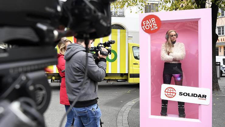 """Eine Videojournalistin filmt die """"Protest-Barbie"""" beim Zürcher Paradeplatz. Mit der Barbie will Solidar Suisse Aufmerksamkeit erregen für die unwürdigen Arbeitsbedingungen, unter denen Spielzeuge wie Barbiepuppen in China produziert werden."""