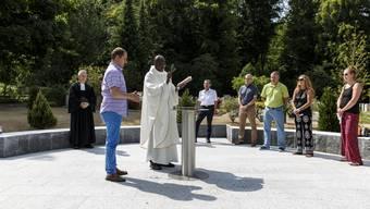 Valentine Koledoye (katholischer Pfarrer) und Ralph Bethke (reformierter Pfarrer) segnen das neue Gemeinschaftsgrab.