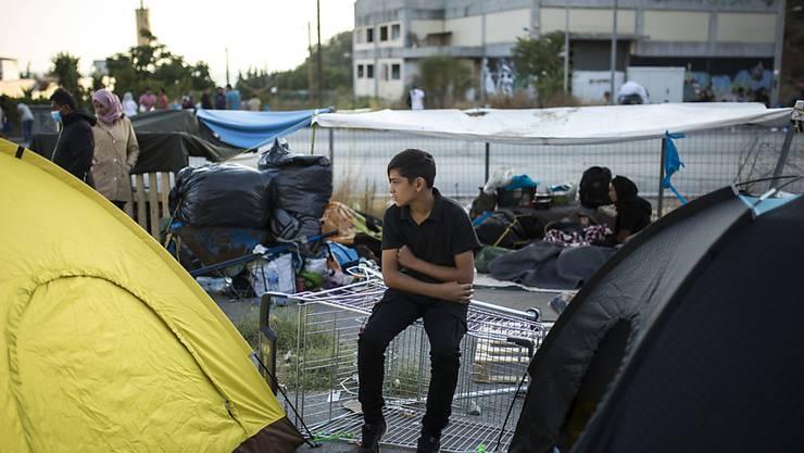dpatopbilder - Ein Kind sitzt in der Nähe des ausgebrannten Flüchtlingslagers Moria. Mehrere Brände haben das Lager fast vollständig zerstört. Laut griechischer Regierung haben Migranten den Brand gelegt. Das Lager ist eigentlich auf 2800 Bewohner ausgelegt, zuletzt lebten dort aber mehr als 12 000 Migranten. Foto: Socrates Baltagiannis/dpa