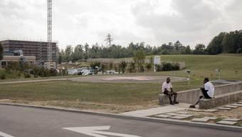 Zwei Asylbewerber sitzen beim Eingang zur unterirdischen Unterkunft, die sich direkt hinter dem Kantonsspital Baden befindet.