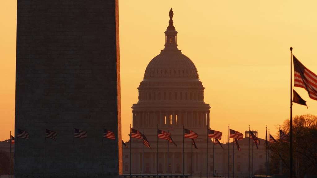 ARCHIV - Das Washington Monument (l) und das Kapitol (M) sind bei Sonnenaufgang zu sehen. Das US-Repräsentantenhaus hat das Veto des amtierenden Präsidenten Trump gegen den Verteidigungshaushalt überstimmt. Foto: Carolyn Kaster/AP/dpa