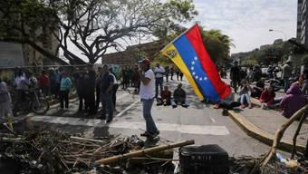 Ein Demonstrant in Caracas trägt eine venezolanische Flagge