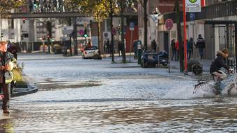 """Ein Kind fährt durch die von Sturmtief """"Herwart"""" überflutete Hafencity in Hamburg. (Bild vom Sonntag)"""