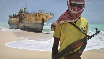 Ein maskierter Pirat vor einem gestrandeten Fischerboot (Archiv)