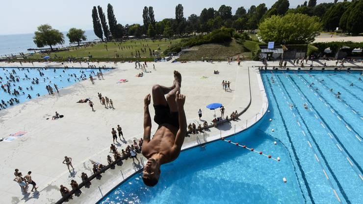 Ein junger Mann springt ins Wasser im Schwimmbad von Lausanne.
