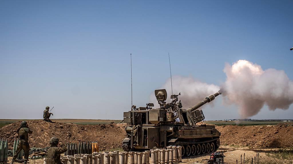 Eine israelische Artillerie feuert von einer Position an der Grenze zwischen Israel und Gaza in der Nähe von Sderot in Richtung des Gazastreifens. Foto: Ilia Yefimovich/dpa
