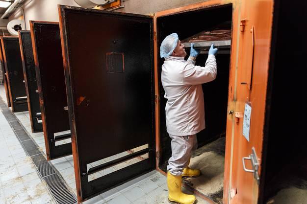 Mitarbeiter stellen den Lachs in die Räucheröfen, wo er 2-4 Tage bleibt